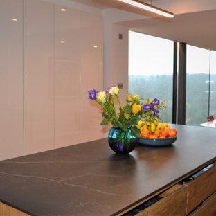 Foto de cocina moderna, de tamaño medio, con suelo de madera en tonos medios, una isla y suelo violeta