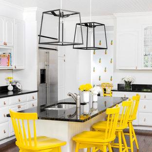 Ejemplo de cocina actual con puertas de armario blancas, electrodomésticos de acero inoxidable, suelo de madera oscura, una isla, fregadero de doble seno y armarios con paneles con relieve