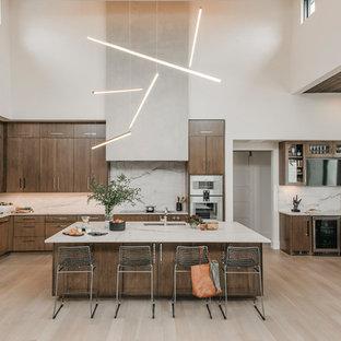 Bild på ett mycket stort funkis vit vitt kök, med en enkel diskho, släta luckor, skåp i mellenmörkt trä, bänkskiva i kvartsit, vitt stänkskydd, stänkskydd i sten, rostfria vitvaror, ljust trägolv och en köksö