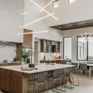 オースティンの巨大なコンテンポラリースタイルのおしゃれなキッチン (シングルシンク、フラットパネル扉のキャビネット、中間色木目調キャビネット、珪岩カウンター、白いキッチンパネル、石スラブのキッチンパネル、シルバーの調理設備、淡色無垢フローリング、白いキッチンカウンター) の写真