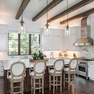 オースティンの広い地中海スタイルのおしゃれなキッチン (ダブルシンク、シェーカースタイル扉のキャビネット、白いキャビネット、白いキッチンパネル、シルバーの調理設備、濃色無垢フローリング、茶色い床、大理石カウンター、大理石のキッチンパネル) の写真