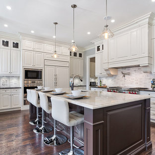 This is an example of a traditional kitchen in Toronto with raised-panel cabinets, an island, a submerged sink, white splashback, integrated appliances, dark hardwood flooring, brown floors, black worktops and beige cabinets.