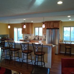 デンバーの中サイズのラスティックスタイルのおしゃれなキッチン (ダブルシンク、シェーカースタイル扉のキャビネット、淡色木目調キャビネット、御影石カウンター、ベージュキッチンパネル、石タイルのキッチンパネル、シルバーの調理設備の、ラミネートの床、ベージュの床) の写真