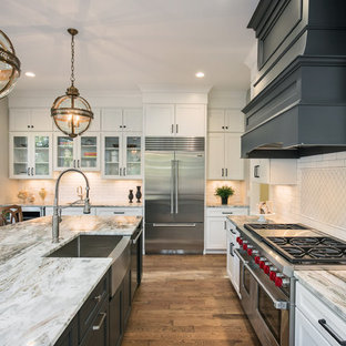 Traditional kitchen designs - Inspiration for a timeless dark wood floor and brown floor kitchen remodel in Grand Rapids with a farmhouse sink, recessed-panel cabinets, white cabinets, granite countertops, white backsplash, subway tile backsplash, stainless steel appliances and an island