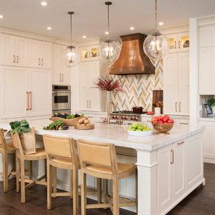 Cette image montre une cuisine américaine traditionnelle en L de taille moyenne avec un évier encastré, un placard à porte shaker, des portes de placard blanches, un plan de travail en marbre, une crédence multicolore, un sol en bois brun et un îlot central.