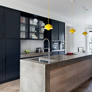 Large contemporary kitchen ideas - Kitchen - large contemporary light wood floor kitchen idea in Dublin with flat-panel cabinets, black cabinets, concrete countertops, an island, a double-bowl sink, white backsplash, subway tile backsplash and black appliances