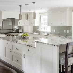 Пример оригинального дизайна: большая, серо-белая угловая кухня в классическом стиле с врезной раковиной, фасадами с утопленной филенкой, белыми фасадами, серым фартуком, фартуком из плитки кабанчик, техникой из нержавеющей стали, темным паркетным полом, островом и коричневым полом