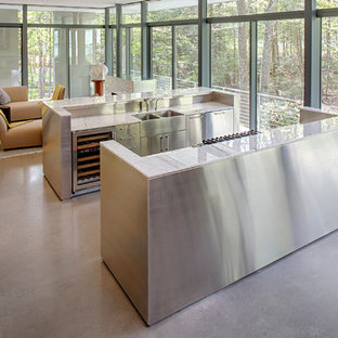 Design ideas for a modern eat-in kitchen in New York with flat-panel cabinets, light wood cabinets, marble benchtops, stainless steel appliances, concrete floors, multiple islands and a double-bowl sink.