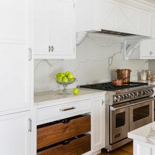 Bild på ett vintage vit vitt kök, med luckor med infälld panel, vita skåp, bänkskiva i kvarts, vitt stänkskydd, stänkskydd i sten, mellanmörkt trägolv och brunt golv