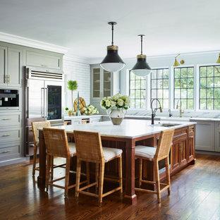ニューヨークの広いカントリー風おしゃれなキッチン (アンダーカウンターシンク、落し込みパネル扉のキャビネット、グレーのキャビネット、大理石カウンター、白いキッチンパネル、セラミックタイルのキッチンパネル、シルバーの調理設備、無垢フローリング、茶色い床、白いキッチンカウンター) の写真