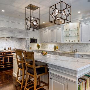 Inredning av ett klassiskt vit vitt l-kök, med en rustik diskho, vita skåp, flerfärgad stänkskydd, stänkskydd i stickkakel, svarta vitvaror, mellanmörkt trägolv och brunt golv