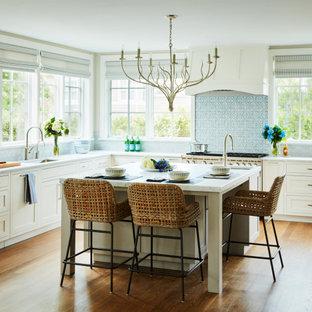 Diseño de cocina comedor en U, clásica renovada, extra grande, con fregadero bajoencimera, armarios estilo shaker, puertas de armario blancas, salpicadero azul, electrodomésticos de acero inoxidable, suelo de madera en tonos medios, una isla, suelo marrón y encimeras grises