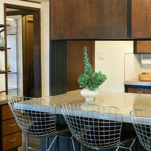 ソルトレイクシティの小さいミッドセンチュリースタイルのおしゃれなキッチン (ドロップインシンク、フラットパネル扉のキャビネット、中間色木目調キャビネット、タイルカウンター、白いキッチンパネル、セラミックタイルのキッチンパネル、黒い調理設備、コンクリートの床) の写真