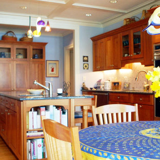 This is an example of a mid-sized arts and crafts u-shaped eat-in kitchen in New York with a double-bowl sink, shaker cabinets, medium wood cabinets, granite benchtops, white splashback, ceramic splashback, stainless steel appliances, medium hardwood floors and with island.