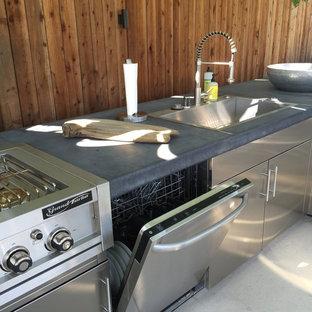 ロサンゼルスの大きいコンテンポラリースタイルのおしゃれなキッチン (ドロップインシンク、フラットパネル扉のキャビネット、ステンレスキャビネット、コンクリートカウンター、シルバーの調理設備の、コンクリートの床) の写真