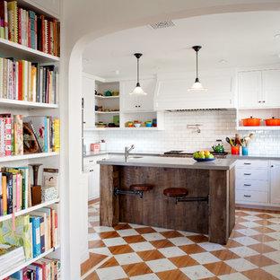 Urige Küche mit weißen Schränken, Küchenrückwand in Weiß, Rückwand aus Metrofliesen und gebeiztem Holzboden in Los Angeles