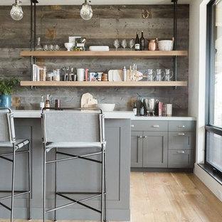 ロサンゼルスの広いトランジショナルスタイルのおしゃれなアイランドキッチン (グレーのキャビネット、珪岩カウンター、茶色いキッチンパネル、木材のキッチンパネル、淡色無垢フローリング、ベージュの床、白いキッチンカウンター、シェーカースタイル扉のキャビネット) の写真