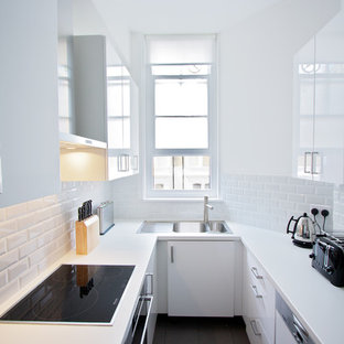 Photo of a mid-sized contemporary u-shaped separate kitchen in London with a double-bowl sink, flat-panel cabinets, white cabinets, laminate benchtops, white splashback, ceramic splashback, ceramic floors, no island and panelled appliances.