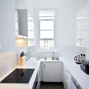Стильный дизайн: узкая отдельная, п-образная кухня среднего размера в современном стиле с двойной раковиной, плоскими фасадами, столешницей из ламината, белым фартуком, фартуком из керамической плитки, полом из керамической плитки, техникой под мебельный фасад и черно-белыми фасадами без острова - последний тренд