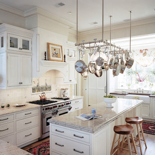 Inspiration for a large timeless u-shaped light wood floor open concept kitchen remodel in Atlanta with beaded inset cabinets, a farmhouse sink, white cabinets, granite countertops, white backsplash, stainless steel appliances and an island