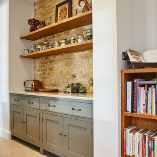 他の地域の大きいカントリー風おしゃれなキッチン (エプロンフロントシンク、インセット扉のキャビネット、グレーのキャビネット、御影石カウンター、ベージュキッチンパネル、サブウェイタイルのキッチンパネル、カラー調理設備、セラミックタイルの床、ベージュの床、ベージュのキッチンカウンター) の写真