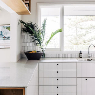 Design ideas for a contemporary l-shaped kitchen in Sydney with a double-bowl sink, white cabinets, white splashback, mosaic tile splashback, a peninsula, black floor, white benchtop and painted wood floors.