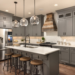 Design ideas for a country l-shaped kitchen in Other with a double-bowl sink, shaker cabinets, grey cabinets, white splashback, subway tile splashback, stainless steel appliances, dark hardwood floors, with island, brown floor and white benchtop.