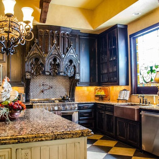 Photo of a large victorian l-shaped kitchen in Dallas with a belfast sink, glass-front cabinets, dark wood cabinets, granite worktops, beige splashback, stone tiled splashback, stainless steel appliances and an island.