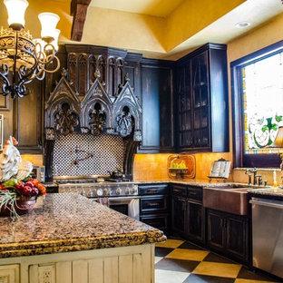 Cette image montre une grand cuisine victorienne en L avec un évier de ferme, un placard à porte vitrée, des portes de placard en bois sombre, un plan de travail en granite, une crédence beige, une crédence en carrelage de pierre, un électroménager en acier inoxydable et un îlot central.
