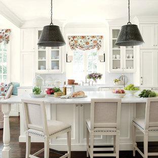 Идея дизайна: кухня в классическом стиле с обеденным столом, раковиной в стиле кантри, фасадами с утопленной филенкой, белым фартуком, фартуком из плитки кабанчик, мраморной столешницей и белыми фасадами