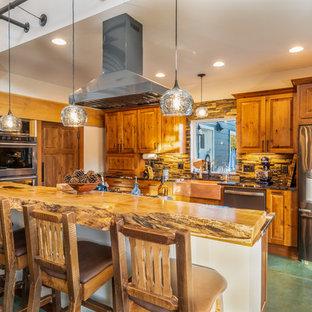 シアトルのラスティックスタイルのおしゃれなキッチン (エプロンフロントシンク、レイズドパネル扉のキャビネット、中間色木目調キャビネット、木材カウンター、茶色いキッチンパネル、石タイルのキッチンパネル、シルバーの調理設備の、緑の床、茶色いキッチンカウンター) の写真