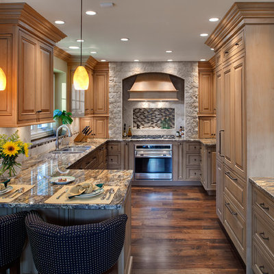 Elegant u-shaped kitchen photo in Chicago with raised-panel cabinets, light wood cabinets and paneled appliances