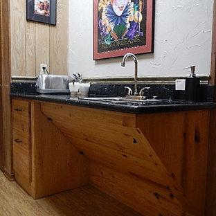 Foto di una cucina abitabile chic di medie dimensioni con ante in legno scuro, top in granito, elettrodomestici in acciaio inossidabile, pavimento in sughero e pavimento beige