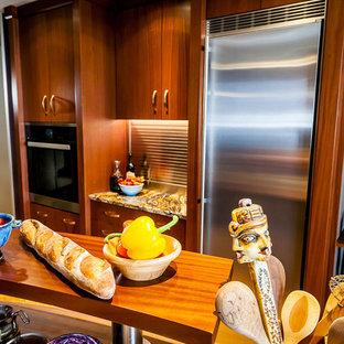 ポートランドの広いエクレクティックスタイルのおしゃれなII型キッチン (エプロンフロントシンク、フラットパネル扉のキャビネット、中間色木目調キャビネット、御影石カウンター、黒いキッチンパネル、大理石のキッチンパネル、シルバーの調理設備、コルクフローリング、紫のキッチンカウンター) の写真