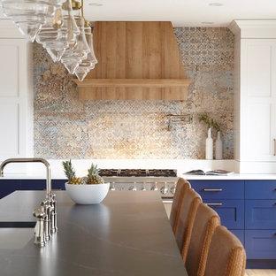Стильный дизайн: огромная п-образная кухня в стиле современная классика с обеденным столом, врезной раковиной, фасадами в стиле шейкер, синими фасадами, столешницей из кварцевого агломерата, техникой под мебельный фасад, светлым паркетным полом, островом, коричневым полом и синей столешницей - последний тренд
