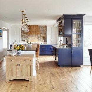 На фото: огромная п-образная кухня в стиле современная классика с обеденным столом, врезной раковиной, фасадами в стиле шейкер, синими фасадами, столешницей из кварцевого композита, техникой под мебельный фасад, светлым паркетным полом, островом, коричневым полом и синей столешницей с