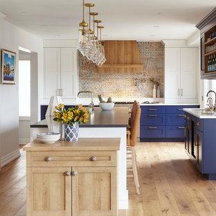 На фото: класса люкс огромные п-образные кухни в стиле современная классика с обеденным столом, врезной раковиной, фасадами в стиле шейкер, синими фасадами, столешницей из кварцевого композита, техникой под мебельный фасад, светлым паркетным полом, островом, коричневым полом и синей столешницей