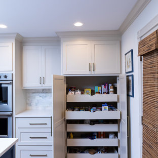 Design ideas for a large open plan kitchen in New Orleans with recessed-panel cabinets, blue cabinets, stainless steel appliances, light hardwood floors, multiple islands, brown floor and white benchtop.