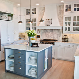Example of a coastal u-shaped kitchen design in Seattle with paneled appliances, a farmhouse sink, glass-front cabinets, white cabinets, marble countertops, white backsplash and marble backsplash