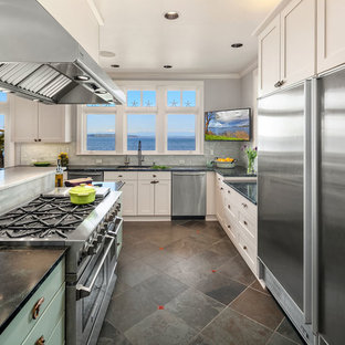 Large beach style open plan kitchen in Seattle with an undermount sink, shaker cabinets, soapstone benchtops, glass tile splashback, stainless steel appliances, slate floors, with island, green floor and green benchtop.