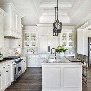 Modelo de cocina en L, tradicional, con fregadero bajoencimera, armarios estilo shaker, puertas de armario blancas, salpicadero blanco, salpicadero de azulejos tipo metro, electrodomésticos de acero inoxidable y una isla