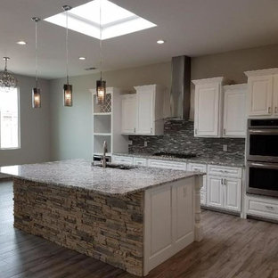 Inspiration for a mid-sized transitional l-shaped medium tone wood floor and brown floor open concept kitchen remodel in Albuquerque with a double-bowl sink, raised-panel cabinets, white cabinets, granite countertops, brown backsplash, matchstick tile backsplash, stainless steel appliances, an island and gray countertops