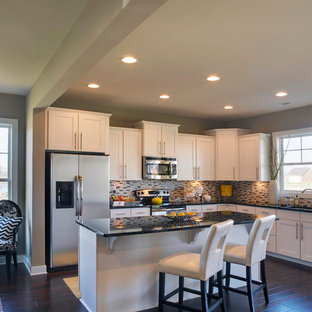 Example of a mid-sized transitional l-shaped open concept kitchen design in Other with shaker cabinets, white cabinets, granite countertops, stainless steel appliances, an island, an undermount sink and beige backsplash