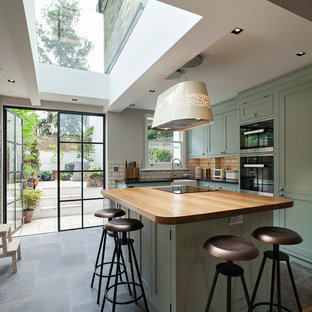 Mid-sized contemporary l-shaped kitchen in London with a farmhouse sink, shaker cabinets, green cabinets, wood benchtops, white splashback, subway tile splashback, black appliances, ceramic floors and with island.