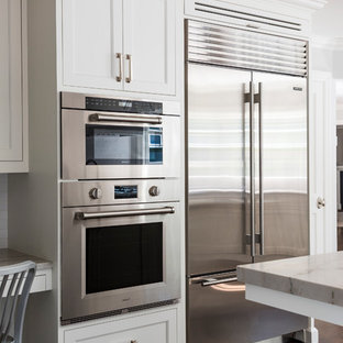 Mid-sized transitional eat-in kitchen remodeling - Mid-sized transitional l-shaped dark wood floor eat-in kitchen photo in New York with an undermount sink, shaker cabinets, white cabinets, quartzite countertops, white backsplash, ceramic backsplash, stainless steel appliances and an island
