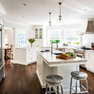 Mid-sized transitional eat-in kitchen designs - Inspiration for a mid-sized transitional l-shaped dark wood floor eat-in kitchen remodel in New York with an undermount sink, shaker cabinets, white cabinets, quartzite countertops, white backsplash, ceramic backsplash, stainless steel appliances and an island