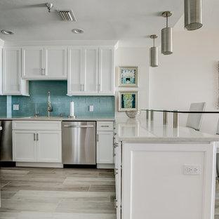 Cette image montre une cuisine marine en L de taille moyenne avec un évier 1 bac, un placard à porte shaker, des portes de placard blanches, un plan de travail en quartz modifié, une crédence bleue, une crédence en carreau de verre, un électroménager en acier inoxydable, un sol en carrelage de porcelaine, une péninsule, un sol beige et un plan de travail multicolore.