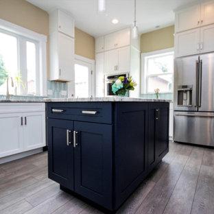 Mittelgroße Klassische Küche in U-Form mit Vorratsschrank, Unterbauwaschbecken, Schrankfronten mit vertiefter Füllung, weißen Schränken, Granit-Arbeitsplatte, Küchenrückwand in Blau, Rückwand aus Keramikfliesen, Küchengeräten aus Edelstahl, dunklem Holzboden, Kücheninsel, braunem Boden und blauer Arbeitsplatte in Providence