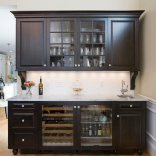 Large traditional eat-in kitchen ideas - Example of a large classic galley light wood floor eat-in kitchen design in Boston with a farmhouse sink, beaded inset cabinets, yellow cabinets, granite countertops, white backsplash, stainless steel appliances and an island