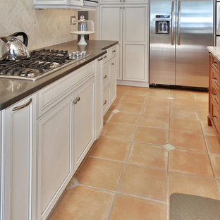 Large transitional enclosed kitchen appliance - Large transitional l-shaped terra-cotta tile enclosed kitchen photo in New York with recessed-panel cabinets, white cabinets, solid surface countertops, gray backsplash, porcelain backsplash, stainless steel appliances and an island